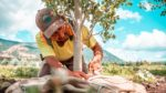Seasonal worker ties up a burlap and basket root ball